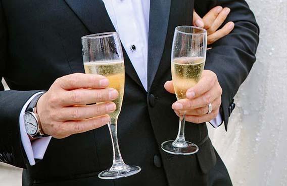 Bräutigam hält Champagnergläser in der Hand