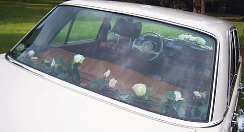 Ranke aus weißen Rosen als Blumenschmuckauf der Hutablage